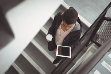 Businesswoman looking at digital tablet on steps