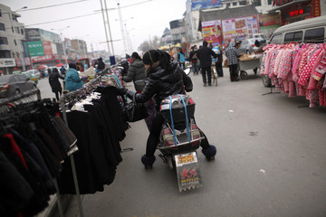 A customer selects clothes at a street stall at the business area of Jiaozuo
