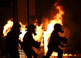 Riot policemen are silhouetted as they run in front of a burning kiosk during clashes in Athens