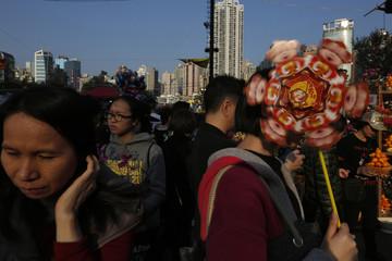 A woman carries a pinwheel featuring monkey faces at a Lunar New Year Fair in Hong Kong