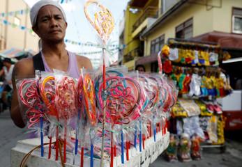 A vendor peddles lollipop candies along a sidewalk in Obando, Bulacan