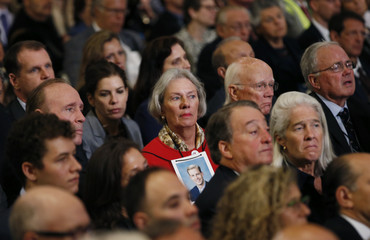 A woman wears a photograph of a victim of the September 11 2001 attacks on the World Trade Center around her neck as she attends the dedication ceremony at the National September 11 Memorial Museum in New York