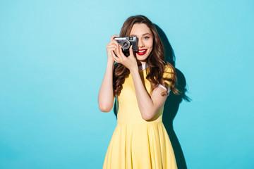 Pretty girl in dress taking photo on a retro camera