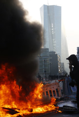 A barricade set up by anti-capitalist 'Blockupy' protesters burns in front of a police cordon near the ECB building before the official opening of its new headquarters in Frankfurt