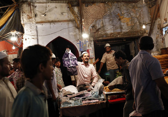 A vendor selling readymade clothes calls out to customers, as Muslims shop ahead of Eid al-Fitr festival in the old quarters of Delhi