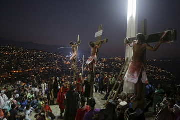 Actors are seen on crosses during a re-enactment of the crucifixion of Jesus Christ in Caracas