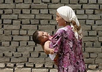 An ethnic Uzbek woman carries a child after crossing the Kyrgyz-Uzbek border, as she returns from Uzbekistan, outside Osh