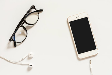 Top view image of smartphone with earphone and glasses.
