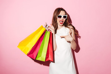 Amazing young brunette woman with shopping bags pointing.