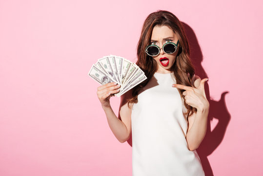 Confused young brunette woman holding money pointing