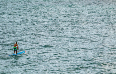 Man on paddle-board in a vast ocean