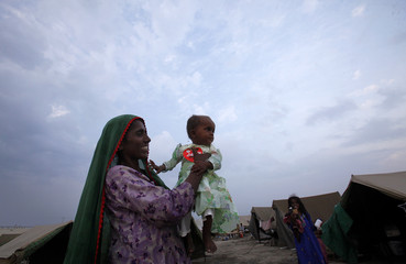 Flood victim holds her baby Aasia, dressed in new clothing donated by a charity organization, as they celebrate Eid-al-Fitr while taking refuge in a relief camp for flood victims in Sukkur