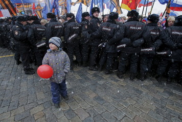 Boy stands in front of Russian police officers during festive concert marking second anniversary of Russia's annexation of Crimea in central Moscow