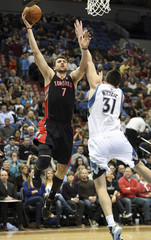 Raptors' Bargnani shoots around Timberwolves' Milicic during the first half of their NBA basketball game in Minneapolis