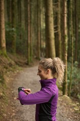 Woman using smart watch in the forest
