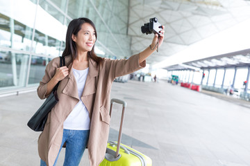 Woman using digital camera taking selfie in airport