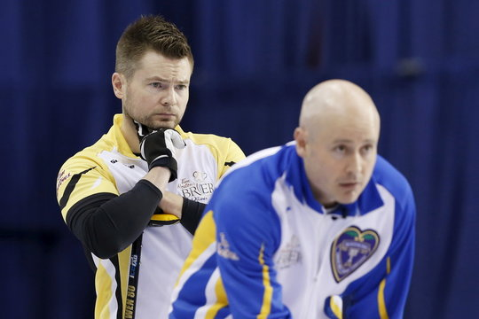 Team Manitoba skip McEwen looks on as Team Alberta skip Koe lines up a shot during their page playoff game at the Brier curling championships in Ottawa