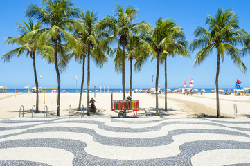 Bright scenic view of Copacabana Beach with palm trees beside the iconic boardwalk in Rio de Janeiro, Brazil