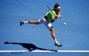 David Ferrer of Spain jumps to hit a return to Tomas Berdych of the Czech Republic during their men's singles quarter-final tennis match at the Australian Open 2014 tennis tournament in Melbourne