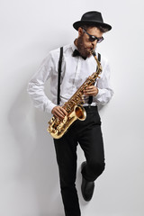 Jazz musician leaning against a wall and playing saxophone