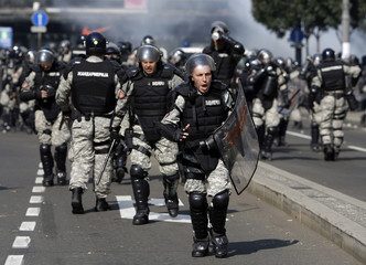 Riot policemen run during clashes with anti-gay protesters in Belgrade