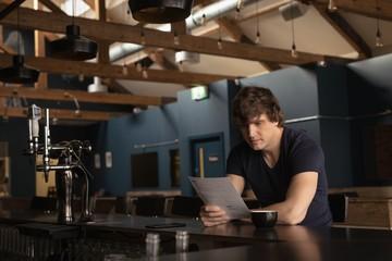 Man looking at menu card while having coffee