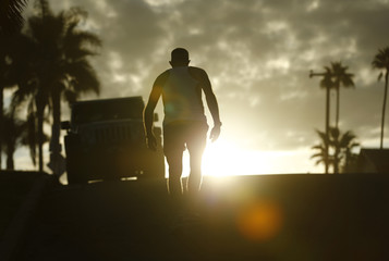 After exercising at the beach, a man makes his way up a hill following his morning workout in Encinitas, California