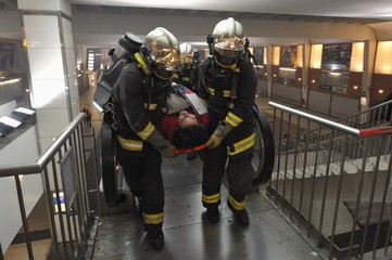 Rescue workers evacuate a volunteer as they participate in a training exercise simulating a nuclear, biological and chemical (NBC)  attack at La Defense metro station, near Paris