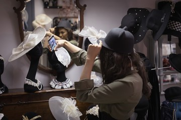 Woman taking selfie while trying hat in jewelry section