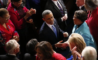 U.S. President Barack Obama shakes hands before delivering his State of the Union address in front of the U.S. Congress in Washington