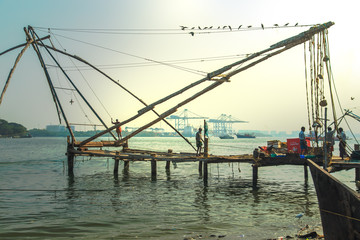 Fishermen are throwing  nets in Fort Kochi.