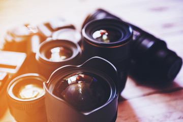Professional camera lenses on a wood background.
