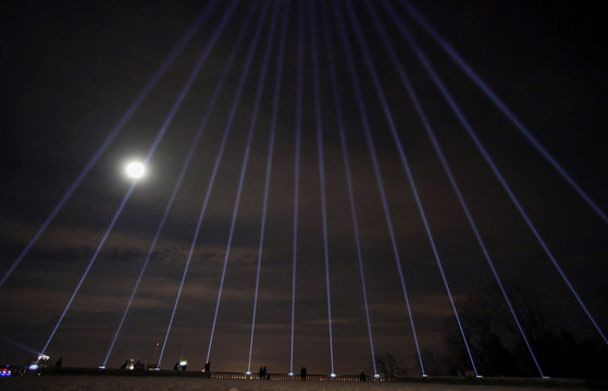 Fourteen beams of light are projected following a vigil to remember the victims of a mass shooting in Montreal