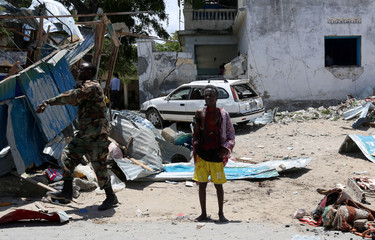 A civilian who was wounded following a car bomb claimed by al Shabaab Islamist militants outside the president's palace stands near the scene of the explosion in the Somali capital of Mogadishu