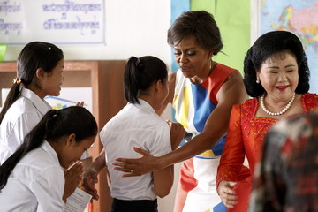 U.S. first lady Michelle Obama and Bun Rany, Cambodia's first lady, hug students during a visit to promote girls' education at a high school on the outskirts of Siem Reap