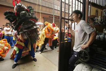 A man watches a lion dance performance in Lima's Chinatown
