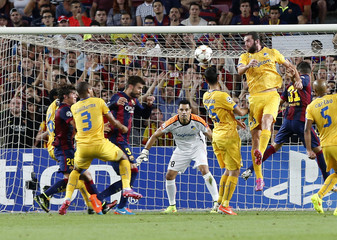 Barcelona's Gerard Pique goes for the ball before scoring his goal against Apoel FC goalkeeper Urko Pardo in Barcelona