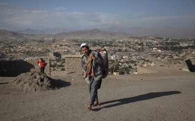 Afghan man carries a bag on his back as he climbs up a hill in Kabul