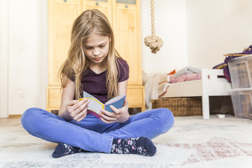 Girl sitting on the floor of children's room reading a book