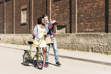 Young couple with bicycle and skateboard taking smartphone selfies
