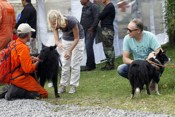 Roselie Kremers and her husband Hans Kremers stroke sniffer dogs after a search in Boquete