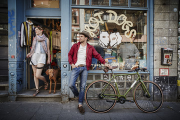 Germany, Hamburg, St. Pauli, Man with bicycle waiting in front of vintage shop, woman with dog coming out