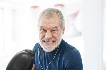 Portrait of aggressive senior man with earphones and boxing gloves in gym