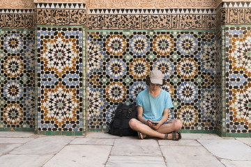 Morocco, Marrakesh, tourist sitting at tiled wall looking at cell phone