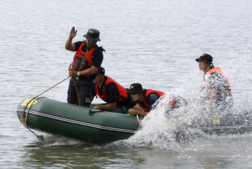 Rescue volunteers look for mock flood victims during a water search and rescue drill at a coastal village in Tanay