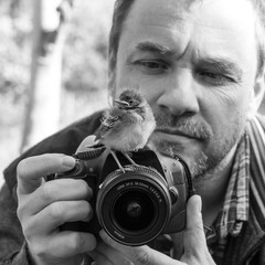 bird and photographer / A photographer with a young songbird on his camera
