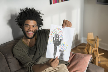 Man sitting on couch in living room showing children's drawing