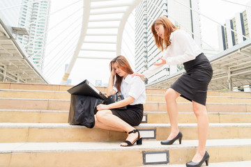 Stressed businesswoman after being dismissed with a colleague clam her down - fired from jobs concept.