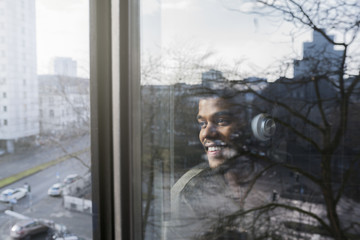 Man at window looking outside listening to music with headphones