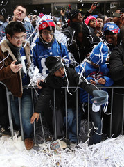 People celebrate during the New York Giants ticker tape Super Bowl victory parade through the Canyon of Heroes along Broadway in New York